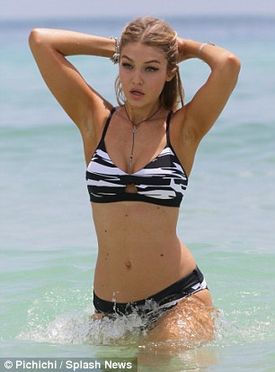 Change of scenery: Gigi edged up her look with the next bikini, modeling a black and white marbled design which featured daring cut-outs