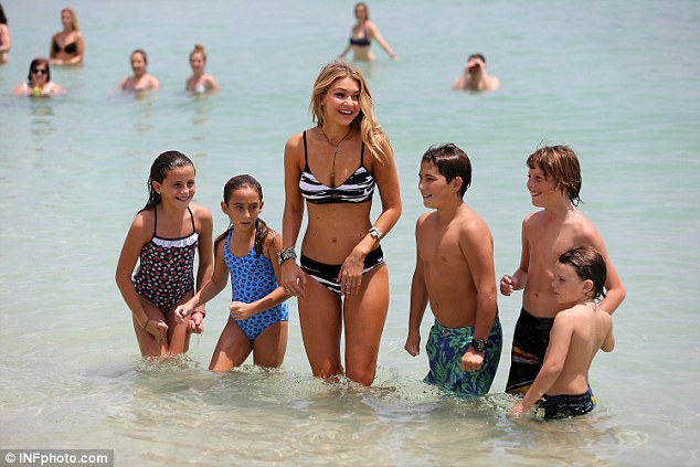 Model behavior: Gigi was later joined on set by five smiling children, sporting colorful, patterned swimsuits