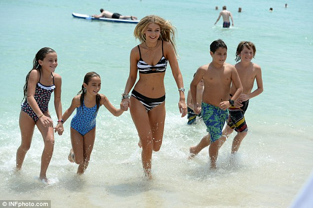All together now: The kids grabbed hands with Gigi and they all ran through the waves together