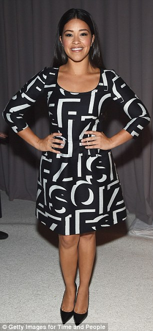 Funky fashion: While Kelly attracted in her bright outfit, Gina Rodriguezrocked a little black dress featuring a smattering of giant 3D letters at the party