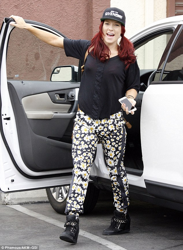 Flower power!Dance pro Sharna Burgess made a splash in floral print trousers featuring a smattering of a daisies along with a trucker hat