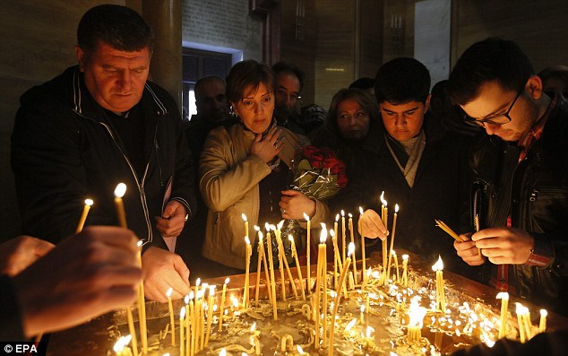 Armenian people light candles as they attend a commemoration ceremony for Armenians who lost their lives during the mass killings at the Temple complex of the Armenian Apostolic Church in Moscow, Russia