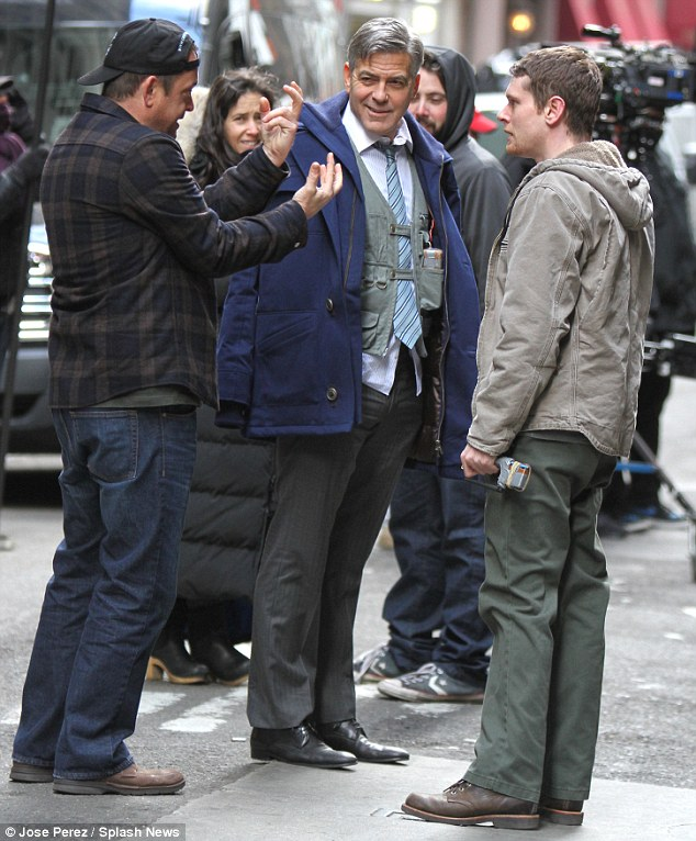 That's more like it: George snapped back to his usual smiley self as he and Kyle listened to comments from a member of the crew. The film is being directed by Jodie Foster