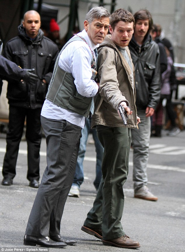 Shooting the scene: George cowered behind a gun-toting Kyle and both looked shocked at something