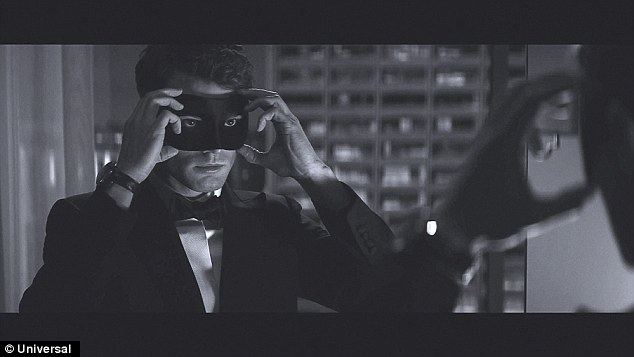 The man behind the masquerade ball mask: Jamie Dornan, 32, continues his mysterious portrayal as Christian Grey in the first still for Fifty Shades Darker