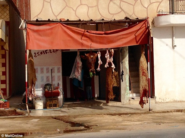 Meat carcasses hang from a shop in Sfax where Malek lived with his mother before his doomed 66ft fishing boat set sail for Italy on Saturday