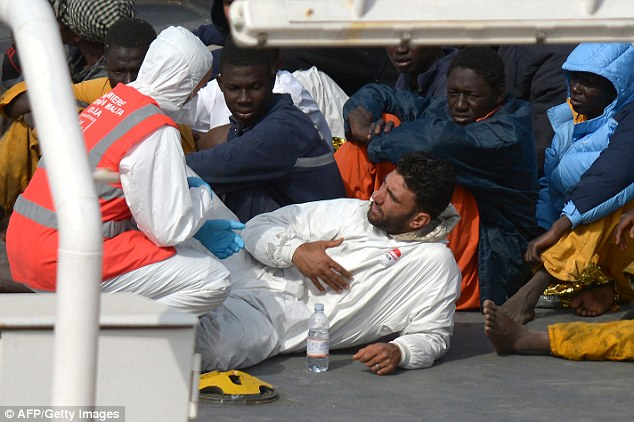 Malek (centre) is seen speaking to a nurse as he lies on deck allegedly pretending he was one of the migrants