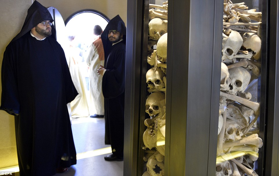 Armenian clerics stand next to the remains of Armenians  at the Armenian Martyrs memorial at the Saint Stephano church  in the Armenian Orthodox Archdeocese of Antelias, north of Beirut