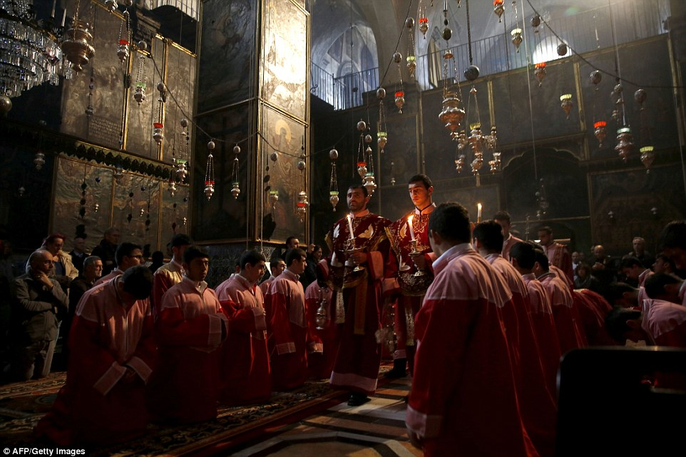 Armenian clergymen hold candles during a special prayer on Friday at the Armenian St. James Cathedral in Jerusalem's Old City
