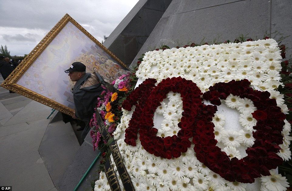 An Armenian police officer carries an icon featuring canonized victims of massacres out of a memorial in Yerevan