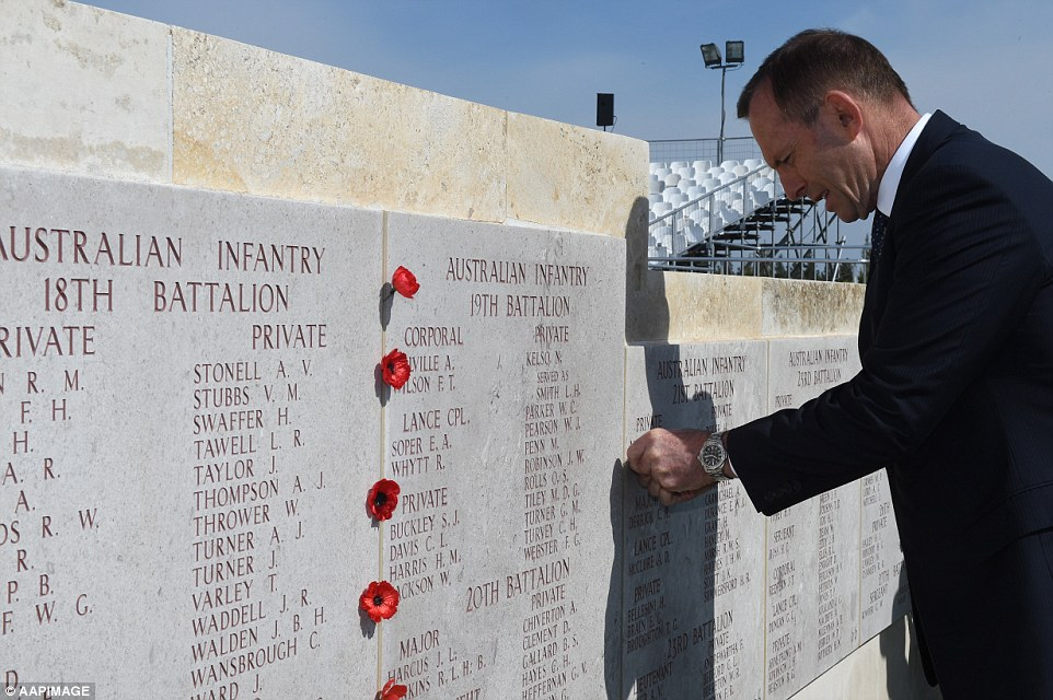 Australian Prime Minister Tony Abbott places a poppy into a memorial wall during a visit at the Lone Pine cemetery on the Gallipoli peninsula