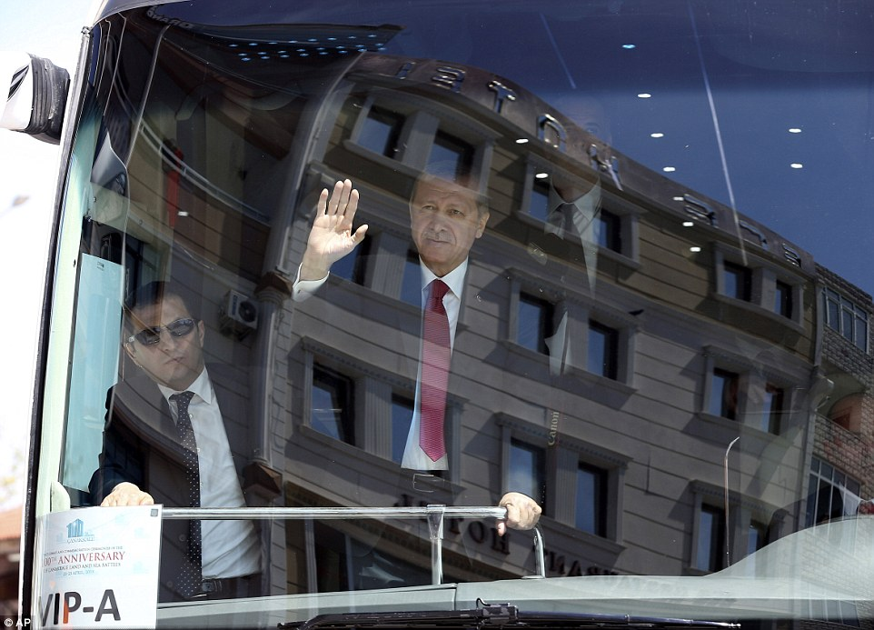 Turkish President Recep Tayyip Erdogan waves to supporters as he travels on a bus through the coastal town of Eceabat in Gallipoli peninsula