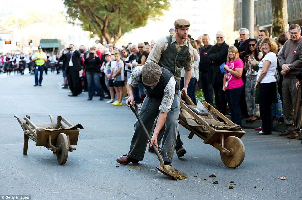 Horse dung is shovelled off the surface of Lambton Quay during the Anzac Day eve street parade in Wellington, New Zealand