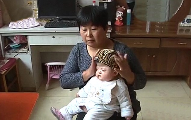Doing her best: MumJiang Min looks after Mengyu at home but is struggling to pay for even food