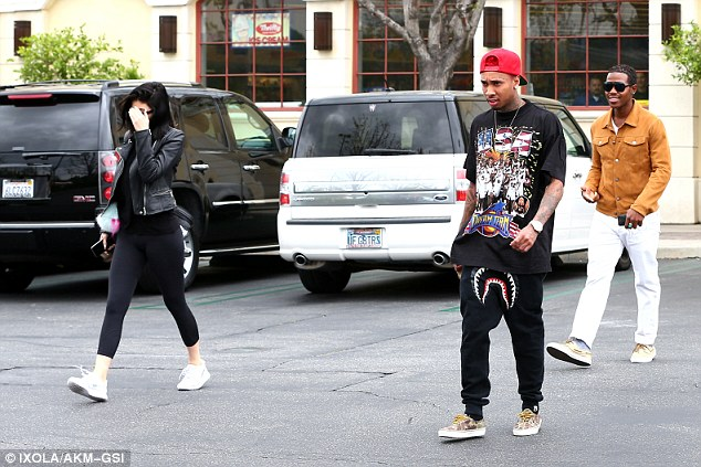 Together: Tyga hid his newly flame coloured hair with a bright red hat as he escorted Kylie back to her car, which the pair arrived in together
