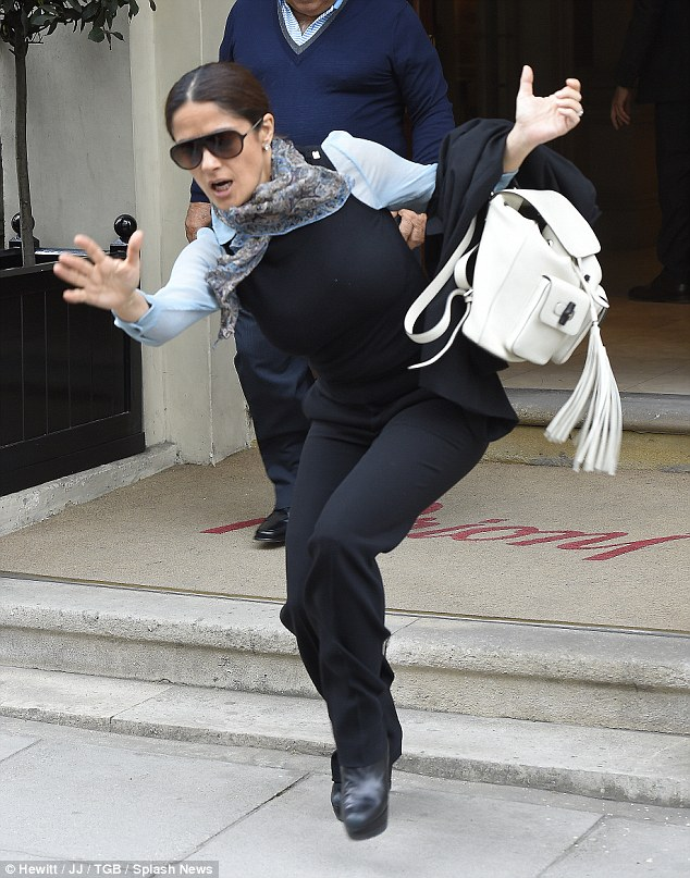 Going, going... Salma Hayek stumbles as she leaves a store in central London on Wednesday afternoon