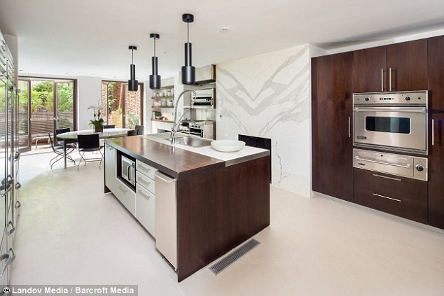 Room for clothes in the oven: The first Garden Floor has a kitchen stocked with stainless steel appliances that contrast to the warm walnut wood eat-in area and access to the tiered garden