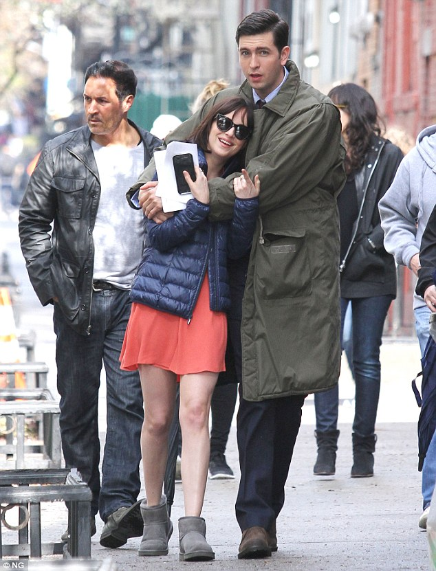 Getting close: Dakota Johnson and Nicholas Braun snuggled up to each other on Thursday as they walked on the New York City set of their upcoming film How To Be Single