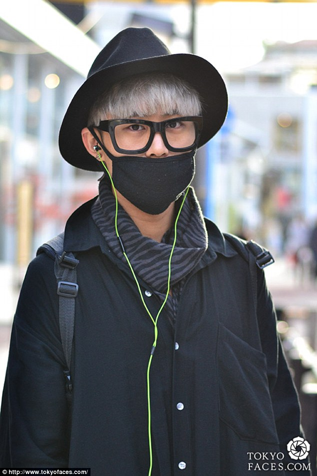 Trendsetter: This model sports a black face mask to complete the look of his dark outfit