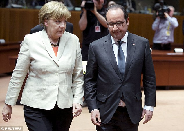 German Chancellor Angela Merkel and French President Francois Hollande arrive at an EU emergency summit in Brussels seeking a solution to the migrants crisis