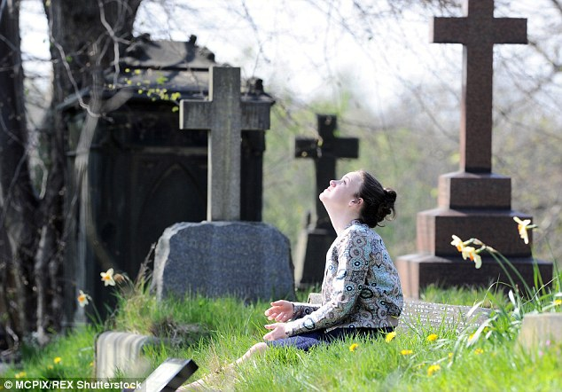 Searching for answers: Windass looked up to the sky as she sat on the grass beside headstones