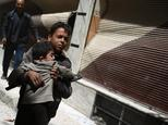 A Syrian boy carries a child while he runs for cover in the rebel-held area of Douma, east of the capital Damascus, as air strikes pound the city on April 22...