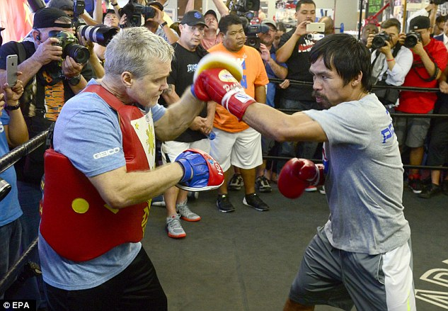 Pacquiao takes on the pads with trainer Freddie Roach in front of the watching media