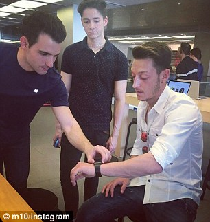 Arsenal midfielder Mesut Ozil (right) took to Instagram to show off his new Apple Watch on Thursday