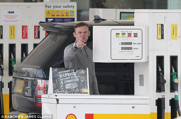 Wayne Rooney doesn't look best pleased after being spotted filling up his £100,000 Range Rover