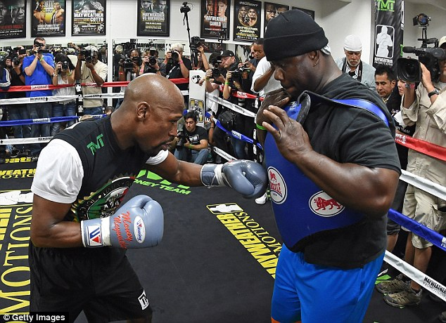 Mayweather works to the body with co-trainer Nate Jones in front of a huge crowd at his gym