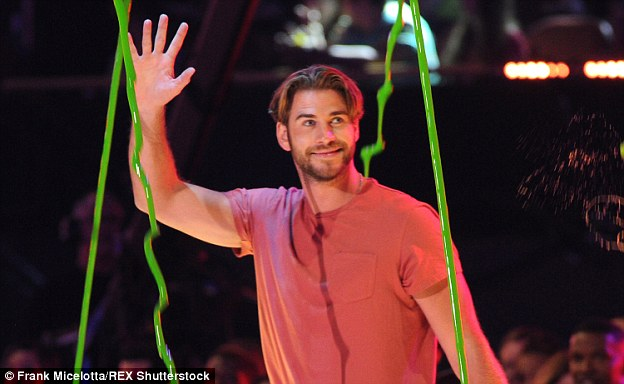 Liam Hemsworth shows off a pair of curtains during an appearance at an awards show last month