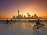A5G2HJ Flying A Kite and bicycling At Sunrise On The Bund Shanghai China