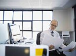 15 Nov 2014 --- Architect reviewing plans in office --- Image by © Hero Images Inc./Hero Images Inc./Corbis