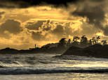 CFC4E8 Storm on Tofino Beach, Canada with lighthouse in silhouette and lone individual on rock in background.