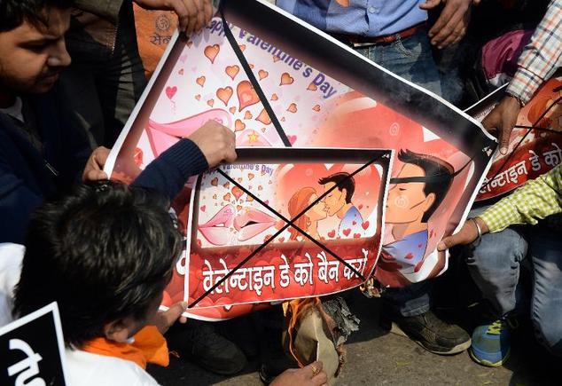 India as a country outlaws kissing in public - here activists from a right-wing Hindu organisation, Hindu Sena, prepare to burn placards promoting Valentine's Day during a protest in New Delhi