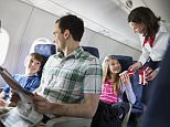 12 Apr 2013, Calgary, Alberta, Canada --- Flight attendant handing out snacks to family in airplane --- Image by © Hero Images/Hero Images/Corbis