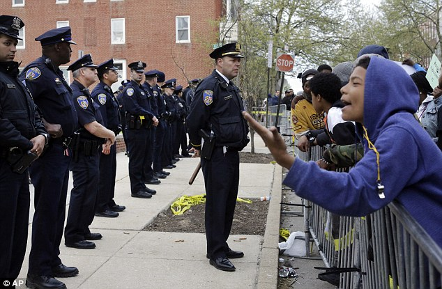 Members of the Baltimore Police Department stand guard outside the department's Western District police station during a protest for Freddie Gray on Thursday