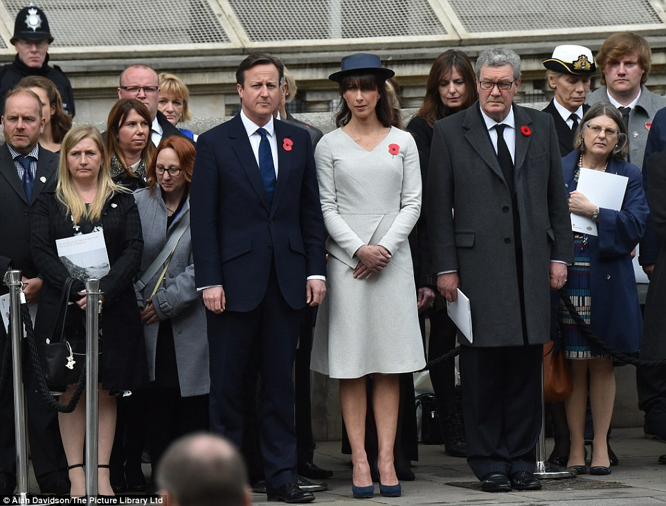 Well turned out: Among a crowd paying their respects, the Prime Minister watches the event with his wife Samantha at his side
