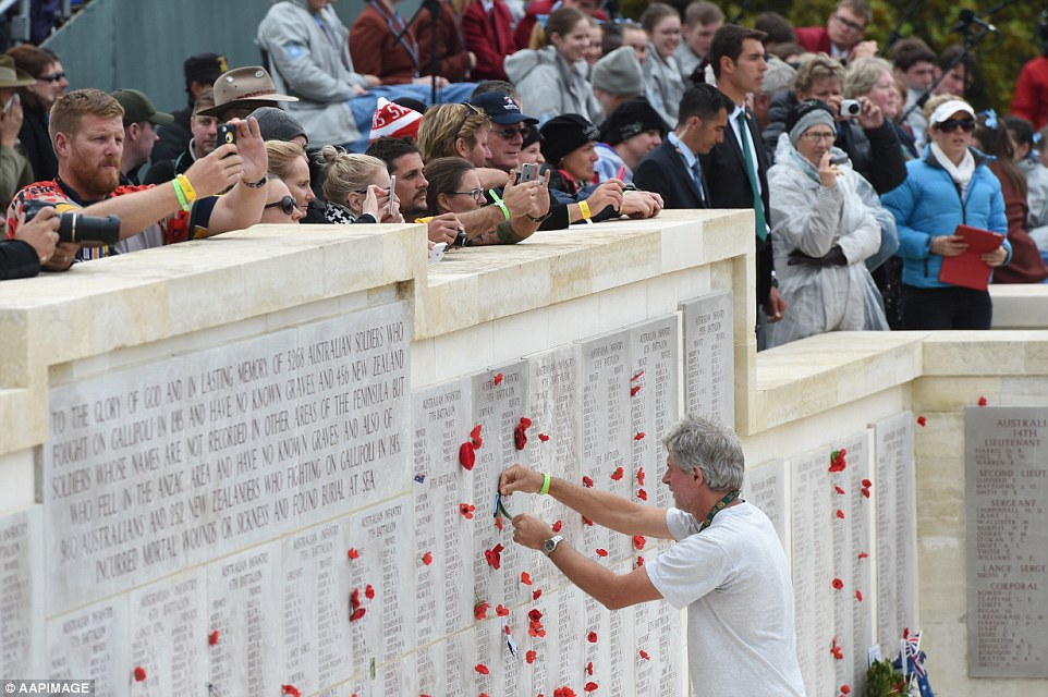 A man places a poppy on the wall of remembrance as thousands of Australians watch the Lone Pine ANZAC Day Centenary service in Turkey