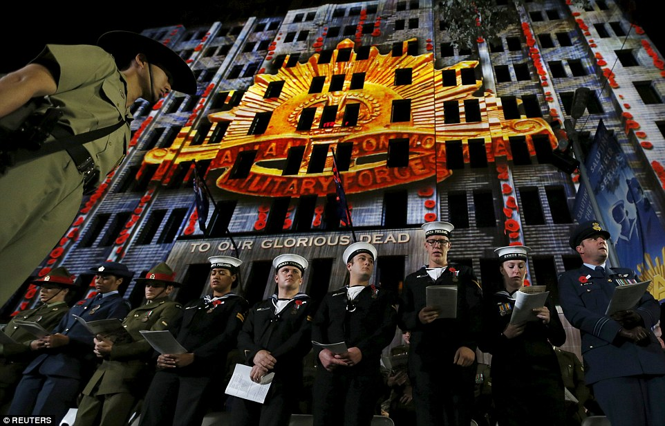 Various branches of New Zealand's defence force stand under a projected image of Australia's Commonwealth Military Force Insignia in Sydney today