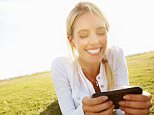 A stock photo of a woman using a smart phone outdoors and reading a text message.
