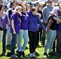 """Students hold hands and remember Maren Sanchez Saturday, April 25, 2015, while listening to live music during the """"Peace Love & Music From Maren"""" event at Jonathan Law High School in Milford, Conn. Saturday's celebration of Maren's life comes exactly one year after the 16-year-old was stabbed to death by a classmate at the high school. (Autumn Driscoll/The Connecticut Post via AP)"""