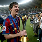 Barcelona's Lionel Messi holds the 2009 FIFA Club World Cup trophy as he celebrates the Spanish club