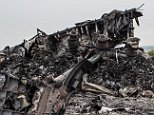 An emergency services worker photographs debris from an Air Malaysia plane crash on July 18, 2014 in Grabovka, Ukraine. Air Malaysia flight MH17 travelling from Amsterdam to Kuala Lumpur has crashed on the Ukraine/Russia border near the town of Shaktersk. The Boeing 777 was carrying 280 passengers and 15 crew members. (Photo by Brendan Hoffman/Getty Images)