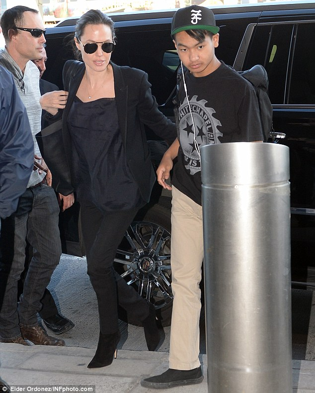 At the airport: Angelina and Maddox stepped out of a black SUV as they arrived at JFK International Airport