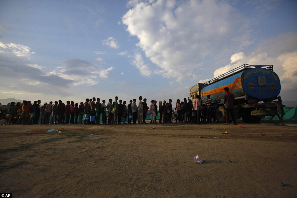 Hundreds queue for a tent in the hope of being given a roof for the night after fleeing what remains of their homes in case they collapse