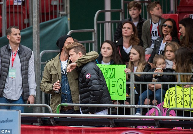 Cheerleaders: David gave his eldest son a big hug while Victoria sat in the stands with Romeo's friends to wait for her son to cross the finish line
