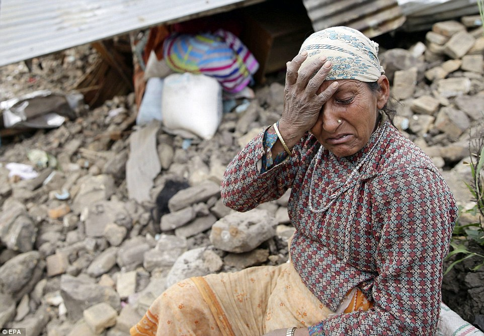 An elderly woman mourns in front of her destroyed home in the Kumalpur village, just outside Kathmandu
