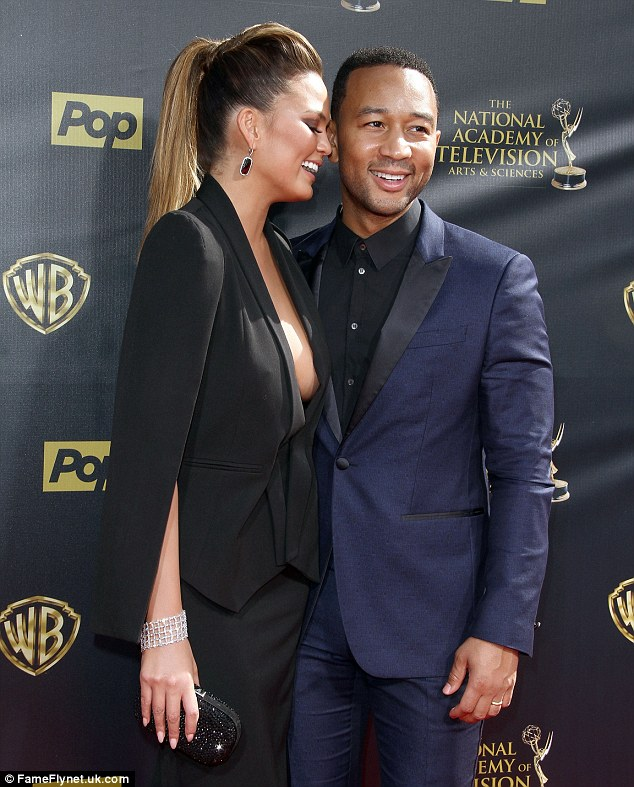 Sweet nothings: Chrissy shared a secret with her husband as she whispered into his ear on the red carpet