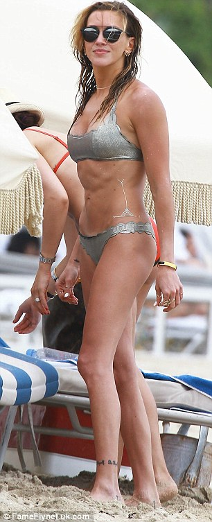 Ab-solutely ripped: The Arrow star flaunted her fantastic figure in a shimmering silver bikini